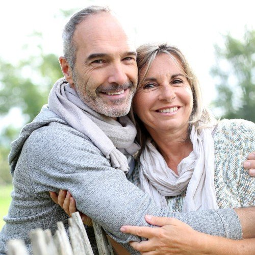 Older man smiling and hugging his wife over top of fence