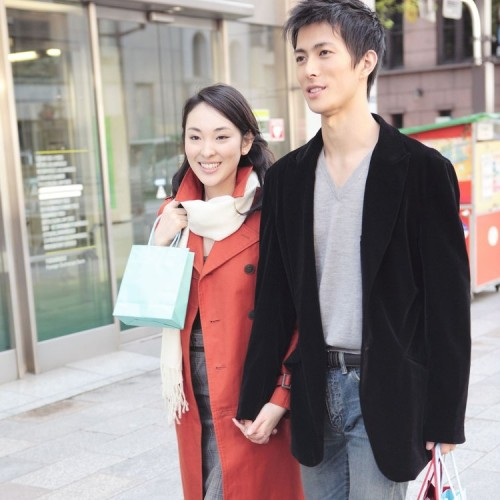 young couple walking down street shopping smiling holding hands