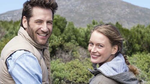 Couple outdoors smiling looking back over shoulders