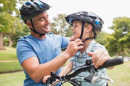 Dad helping boy on bike with helmet