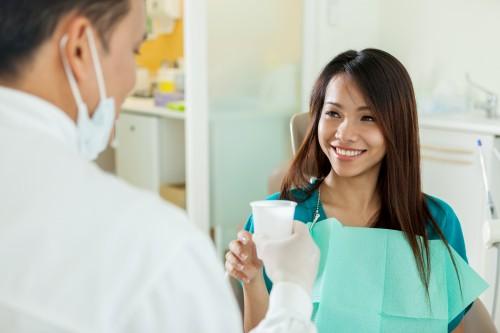 dentist handing patient a glass of water