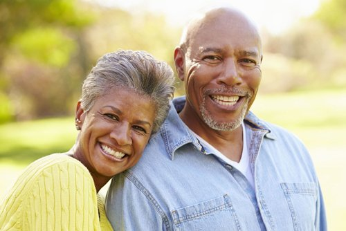 Elderly man and woman with healthy smiles hugging in park during fall season