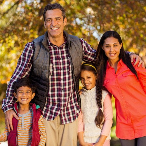 family hugging close and smiling for fall family portrait