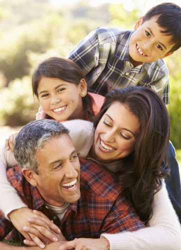 Family piled on dad laughing in park