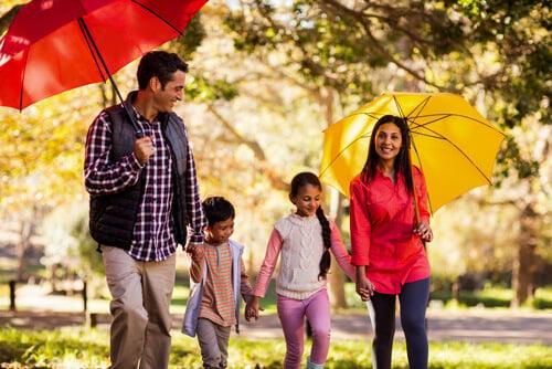 family walking through fall park smiling holding umbrellas