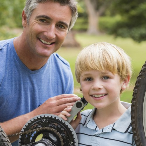 Father and son smiling while fixing a bike