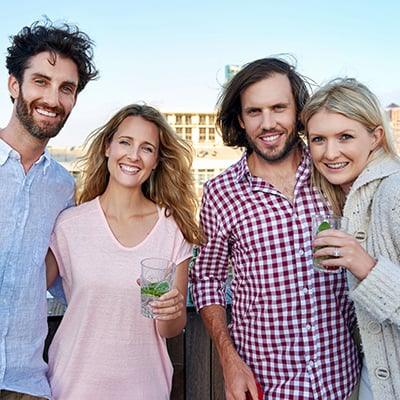 Two couples looking at camera and smiling holding glasses of water with mint