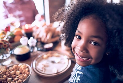 Little girl looking back and smiling at thanksgiving table