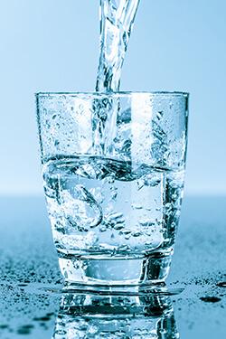 A glass of splashing ice water reminding you to enjoy fresh water on a regular basis.