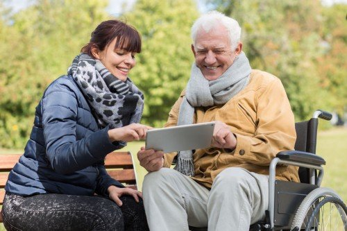 Young woman helping elderly man in wheelchair outdoors with tablet