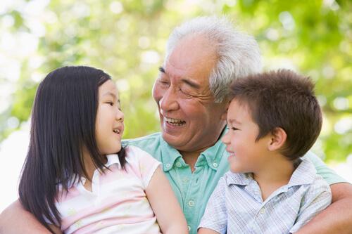 grandpa smiling holding two grandchildren