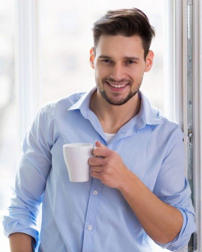Man happily drinking coffee and smiling