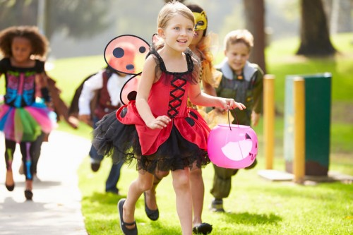group of kids dressed in Halloween costumes running to a house