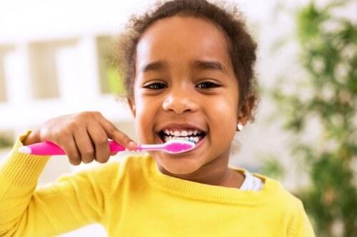 little girl brushing her teeth looking in the mirror