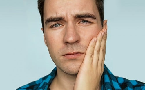 Man holding his cheek from discomfort