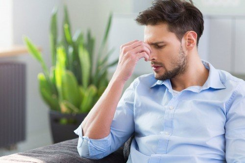 man rubbing forehead from headache