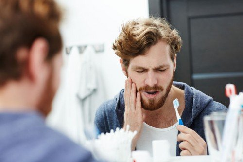 Man holding jaw from tooth sensitivity looking in a bathroom mirror