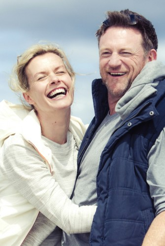 Middle age couple laughing hugging on beach