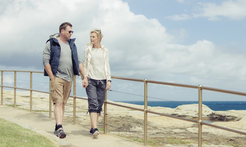 Middle age couple walking down to beach