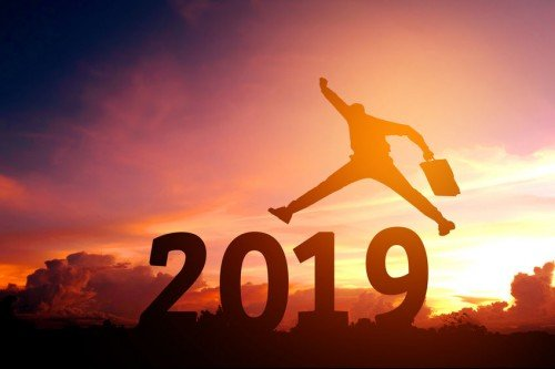 2019 with man jumping excited in sunset