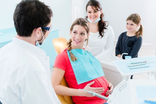Pregnant woman sitting in dental chair smiling at her doctor