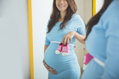 Pregnant woman smiling in mirror holding baby shoes