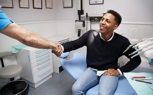 young man shaking hand with his dentist after treatment