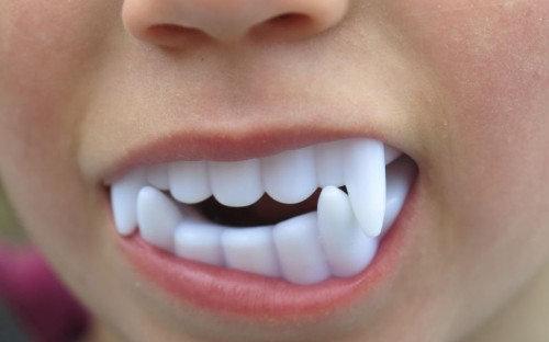 kid with vampire teeth toy in mouth