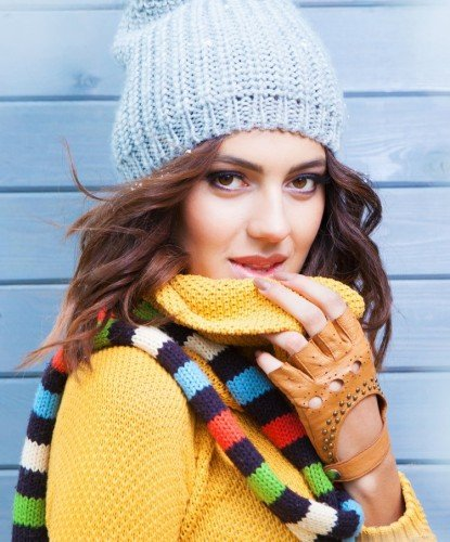 Woman in yellow sweater pulling collar down from covering her face