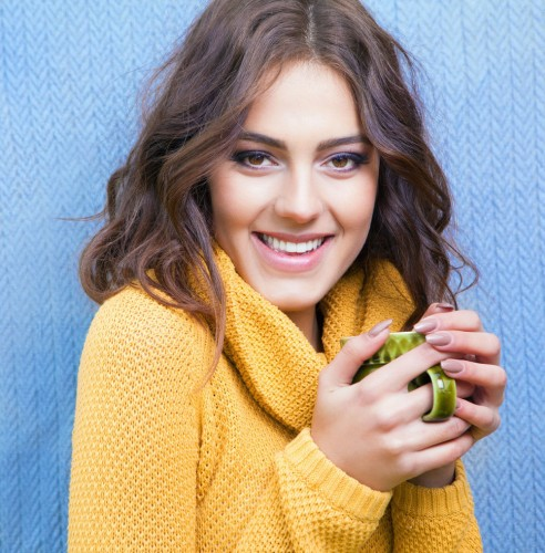 Woman in yellow sweatshirt smiling holding a warm cup of coffee