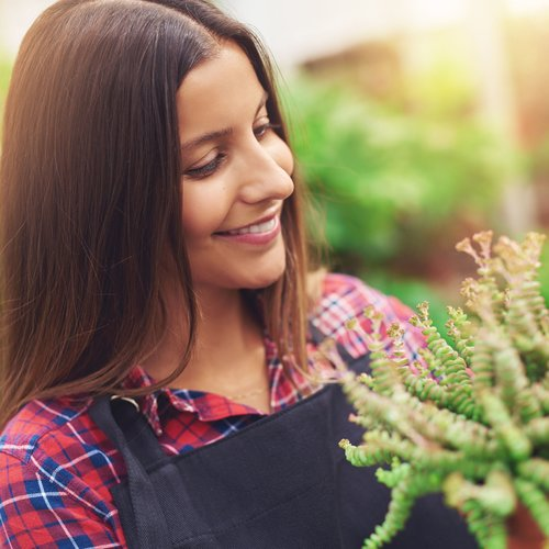 Woman smiling at her flowers in her greenhouse