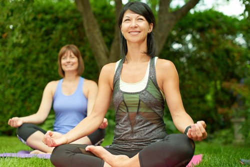 A woman doing yoga who is happy with her smile