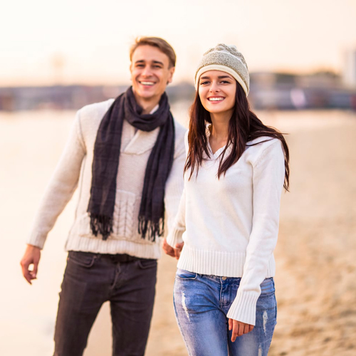 Young couple walking down the beach smiling holding hands
